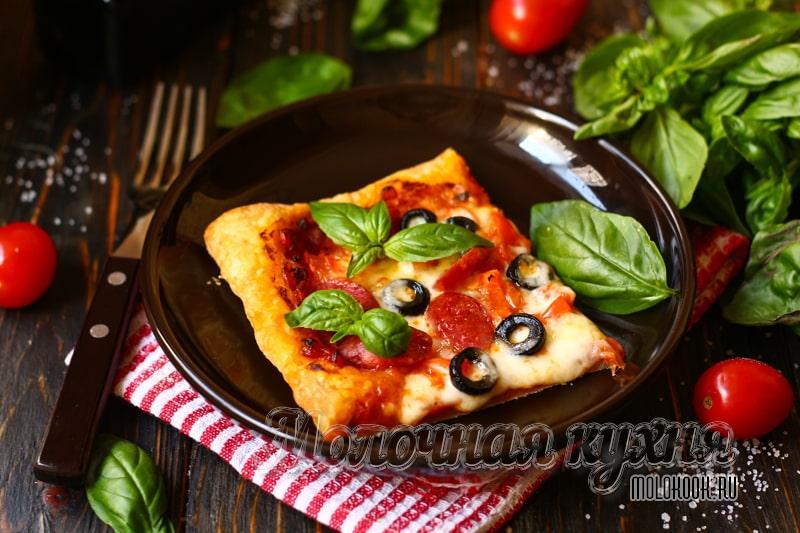 Хрустящая пицца из слоеного теста с начинкой из колбасок, маслин и сыра
