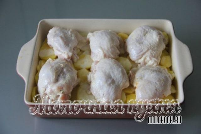 Куриные бедра выложены поверх картофеля