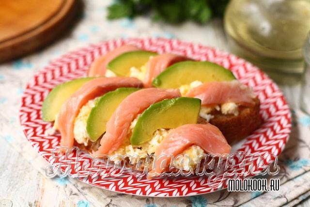 Ломтики авокадо и лосося выложены на бутерброды