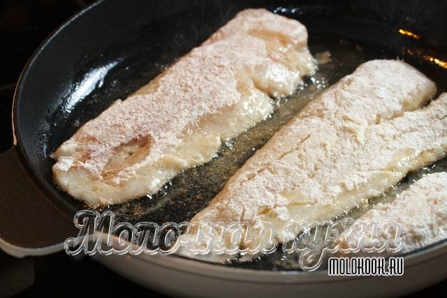 Запанированная рыба готовится в сковородке